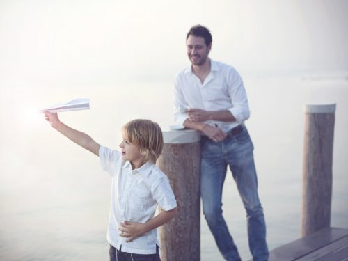 proud Father looks his son who is flying his paper airplane